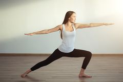 Young woman wearing white tank top working out, doing yoga exercise. Young woman wearing white tank top doing yoga exercise. Standing in Warrior one pose Stock Photos