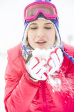 Young woman wearing winter coat blowing snow outdoors Stock Photo
