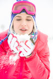 Young woman wearing winter coat blowing snow outdoors Royalty Free Stock Images