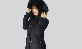 Young woman wearing winter coat with the faux - fur hood Stock Photos