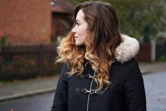 Young woman wearing winter coat on suburban street Stock Photography