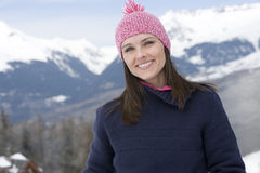 Young woman wearing woolen hat in snow, smiling, portrait, mountain range in background Stock Image