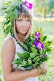 Young woman wearing wreath of flowers and bouquet Stock Photos