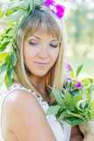Young woman wearing wreath of flowers and bouquet. In the summer park Stock Photo