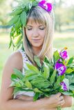 Young woman wearing wreath of flowers and bouquet. In the summer park Stock Images