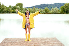 Young woman wearing a yellow raincoat in the rain Royalty Free Stock Images