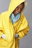 Young Woman Wearing Yellow Raincoat In Studio Stock Photo