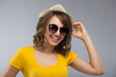 Young woman wearing yellow shirt hat and jeans shorts  make face Royalty Free Stock Images