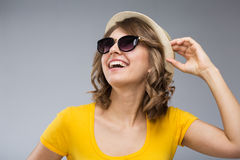 Young woman wearing yellow shirt hat and jeans shorts  make face Royalty Free Stock Image