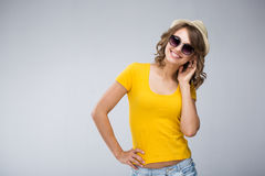 Young woman wearing yellow shirt hat and jeans shorts  make face. S over grey background Stock Photography