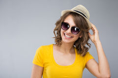 Young woman wearing yellow shirt hat and jeans shorts  make face Royalty Free Stock Photos