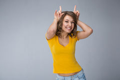 Young woman wearing yellow shirt and jeans shorts  over grey bac. Image of young woman wearing yellow shirt and jeans shorts  make faces over grey background Royalty Free Stock Photos