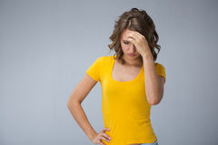 Young woman wearing yellow shirt and jeans shorts  over grey bac. Image of young woman wearing yellow shirt and jeans shorts  make faces over grey background Stock Images