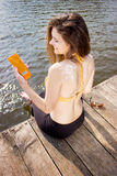 Young woman  wearing in yellow swimsuit with sun shape on the shoulder on the beach Royalty Free Stock Images