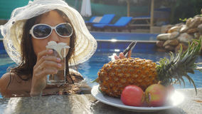 Young woman wears hat and sunglasses drinking water while sunbathing in the pool at plate with fruits and plumeria. Young woman drinking water while sunbathing Stock Photo