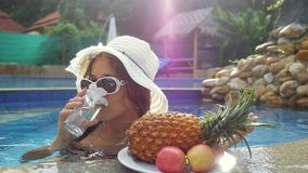 Young woman wears hat and sunglasses drinking water while sunbathing in the pool at plate with fruits and plumeria stock footage