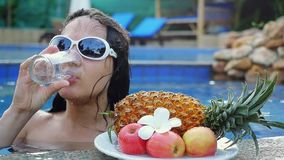 Young woman wears sunglassed drinks water while sunbathing in the pool at plate with fruits and plumeria flower in slow stock footage