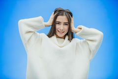 A young woman wears a winter sweater on an isolated blue background, smiling in love, raising her hand up from surprise. Puts her head on. Nice girl royalty free stock image