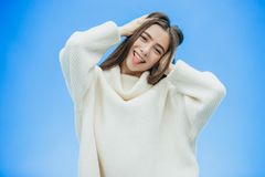 A young woman wears a winter sweater on an isolated blue background, smiling in love, raising her hand up from surprise. Puts her head on. Nice girl royalty free stock images