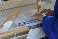 Young woman weaves a white cloth on a hand wood loom. Traditional Russian folk art royalty free stock image