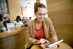 Young woman websurfing on tablet in coffee shop Stock Photo