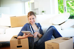 Young woman websurfing on tablet recently moved in Stock Image