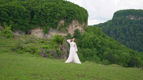 A young woman in a wedding dress and black boots posing in the mountains.