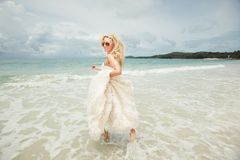 Young woman in wedding dress running over sea turning back. lucky and funny bride on the beach. Young woman in wedding dress goes over sea turning back. bride Stock Photo