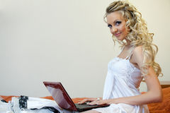 Young woman with wedding dress and laptop. Stock Image