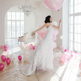 Young woman in wedding dress in luxury interior flies on pink and white balloons. Royalty Free Stock Image