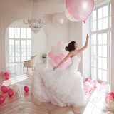 Young woman in wedding dress in luxury interior flies on pink and white balloons. Charming young bride brunette with short haircut in stylish Quinceanera royalty free stock images
