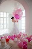 Young woman in wedding dress in luxury interior with a mass of pink and white balloons. Stock Photography