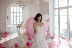 Young woman in wedding dress in luxury interior with a mass of pink and white balloons. Charming young bride brunette with short haircut in stylish Quinceanera Royalty Free Stock Images