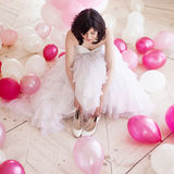Young woman in wedding dress in luxury interior with a mass of pink and white balloons. Hold in hands her white shoes Royalty Free Stock Photography