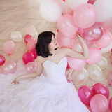 Young woman in wedding dress in luxury interior with a mass of pink and white balloons. Royalty Free Stock Photos