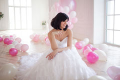 Young woman in wedding dress in luxury interior with a mass of pink and white balloons. Stock Photos
