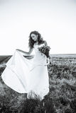 Young woman in wedding dress outdoors. Beautiful bride in a field at sunset. Black and white Stock Images