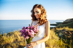 Young woman in wedding dress outdoors. beautiful bride in a field at sunset Royalty Free Stock Image