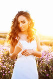 Young woman in wedding dress outdoors. beautiful bride in a field at sunset Stock Photo