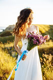 Young woman in wedding dress outdoors. beautiful bride in a field at sunset. Young happy women in wedding dress outdoors. beautiful bride in a field at sunset Royalty Free Stock Image