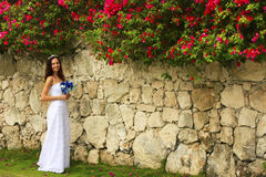 Young woman in wedding dress posing in front of the stone wall Stock Image