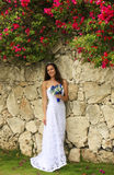 Young woman in wedding dress posing in front of the stone wall Stock Photos