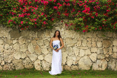 Young woman in wedding dress posing in front of the stone wall Stock Images
