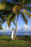 Young woman in wedding dress standing by palm tree Royalty Free Stock Images