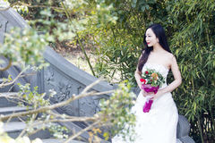 A young woman wedding photo/portrait sit on an ancient old bridge in Shanghai shui bo parkpark of water. Shot in park of water Shanghai shui bo park in Shanghai Stock Image
