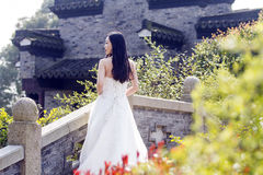 A young woman wedding photo/portrait stand on a ancient old bridge. Shot in park of water in Shanghai, we call it `shui bo park`, a young woman wedding photo/ Stock Image