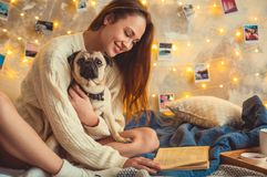 Young woman weekend at home decorated bedroom with dog reading book stock image
