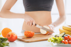 Young woman weight loss perfect body shape. Young female weight loss standing in the kitchen cutting apple Royalty Free Stock Images