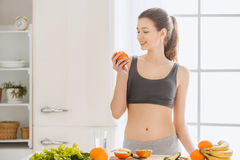 Young woman weight loss perfect body shape. Young female weight loss standing in the kitchen eating apple Stock Images
