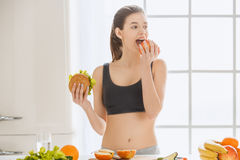 Young woman weight loss perfect body shape. Young female weight loss standing in the kitchen eating apple Royalty Free Stock Photos